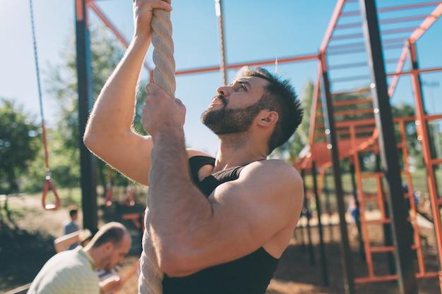 Barbudo, com cabelo preto homem escalando corda grossa durante exercícios de fitness em cross-fit treinamento com. mãos fortes e musculosas.