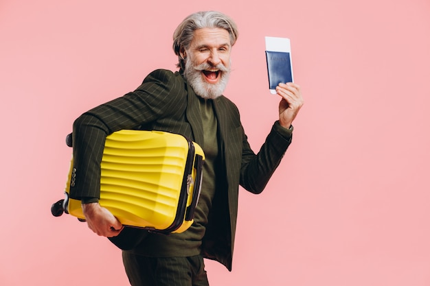 Barbudo elegante homem de meia idade, segurando uma mala amarela e passaporte com um bilhete na rosa.