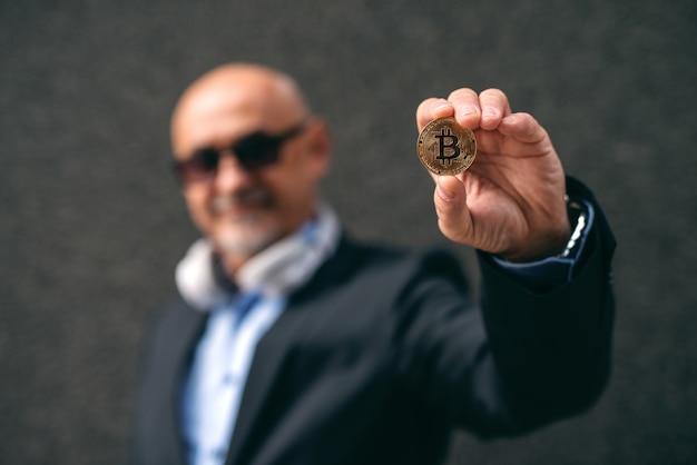 Barbudo empresário rico adulto sênior segurando bit-moeda.