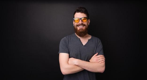 Barbudo feliz usando óculos escuros elegantes, cruzando as mãos e sorrindo para a câmera sobre um fundo escuro
