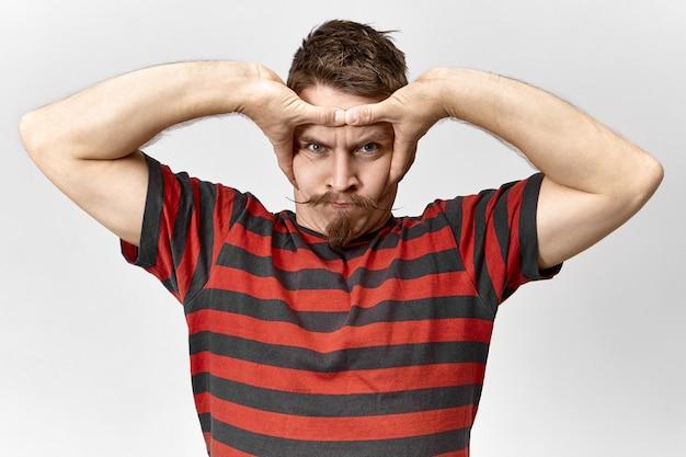 Barbudo furioso vestindo uma camiseta listrada com expressão facial mal-humorada e descontente apertando a cabeça com as duas mãos, sofrendo de dor de cabeça, perdendo a paciência, zangado com sons ou ruídos altos