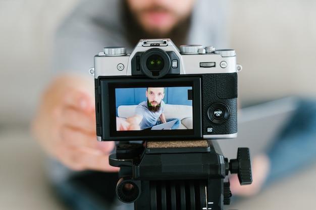 Barbudo gravando um vídeo de si mesmo usando a câmera no tripé e criando conteúdo para mídias sociais.
