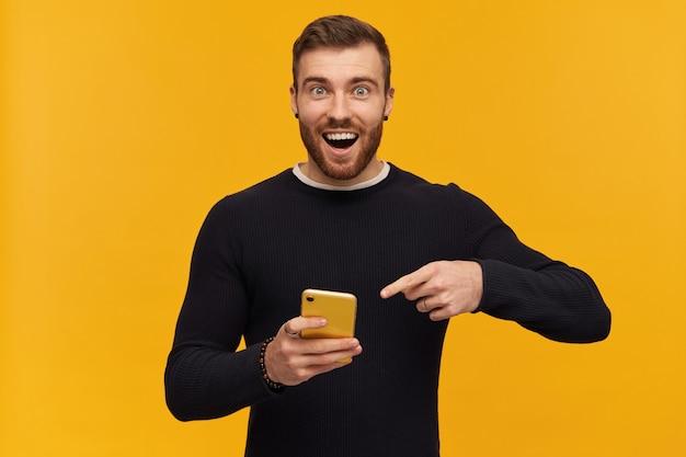 Barbudo, homem de aparência feliz com cabelo castanho. tem piercing. vestindo um suéter preto. segurando e apontando o dedo para smartphone, copie o espaço. isolado sobre a parede amarela