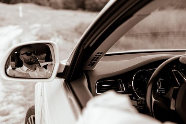 Barbudo homem de negócios caucasiano olhando para a câmera através do espelho retrovisor, cabeça e ombros