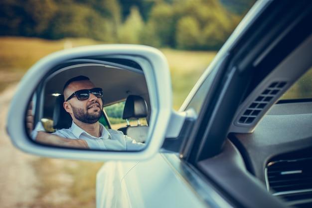 Barbudo homem de negócios caucasiano olhando para a câmera pelo espelho retrovisor. fundo de verão.