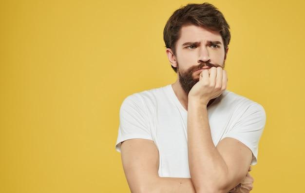 Barbudo homem em problemas de emoção de estúdio de fundo amarelo de camiseta branca. foto de alta qualidade