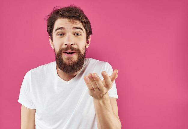 Barbudo homem em um estúdio de expressão facial feliz de camiseta branca. foto de alta qualidade