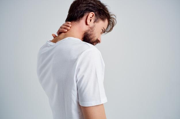 Barbudo homem em uma t-shirt branca estresse remédio dor no pescoço luz de fundo. foto de alta qualidade