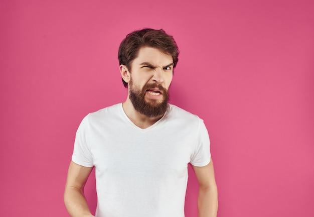 Barbudo homem em uma t-shirt branca fundo rosa de gestos de mão. foto de alta qualidade