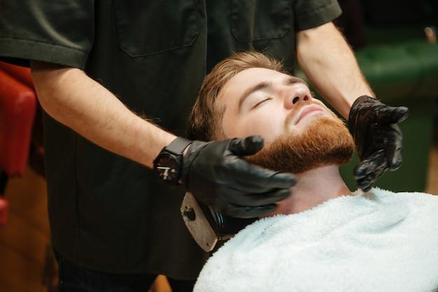 Barbudo homem ficando barba raspando por cabeleireiro enquanto está na cadeira de barbearia.