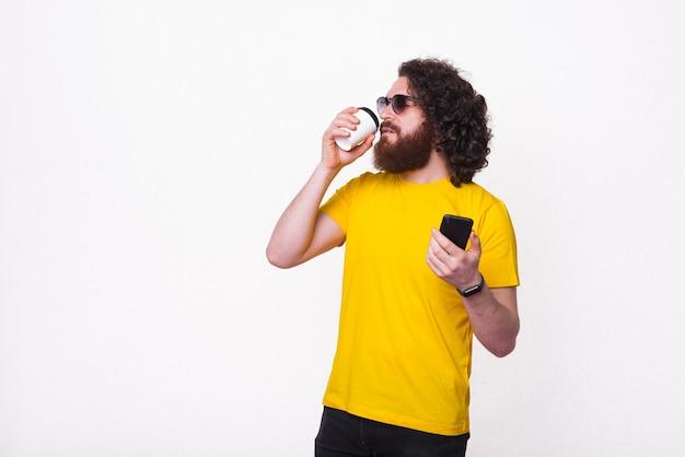 Barbudo homem hippie em camiseta amarela tomando café e segurando um smartphone