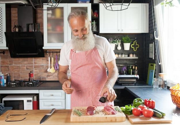 Barbudo homem sênior cozinhar bifes em sua cozinha.