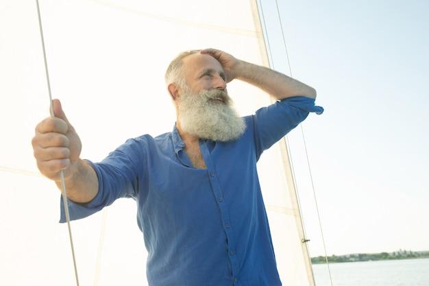 Barbudo homem sênior no barco à vela ou iate flutuando no lago.