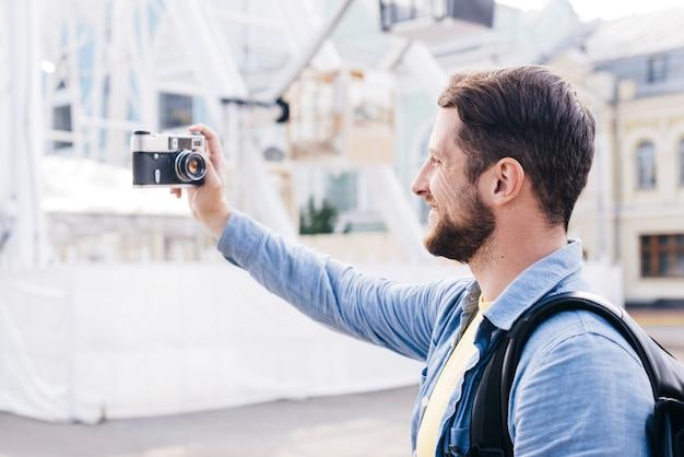 Barbudo homem sorridente tomando selfie com câmera retro durante a viagem