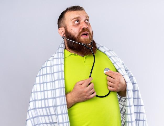 Barbudo insalubre enrolado em cobertor sentindo-se mal, sofrendo de frio, ouvindo seus batimentos cardíacos usando um estetoscópio parecendo preocupado