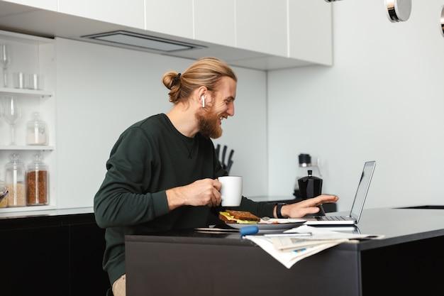 Barbudo jovem bonito sentado na cozinha tomando café usando o computador portátil.