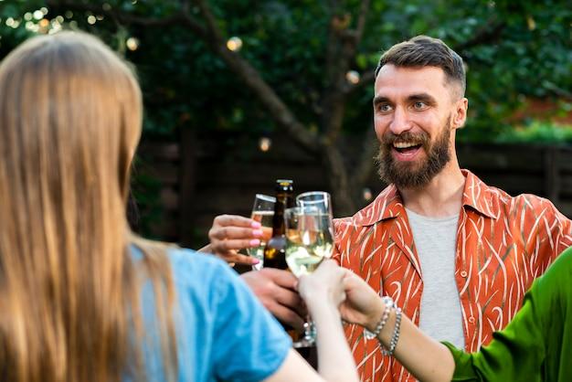 Barbudo jovem brindando bebidas com amigos