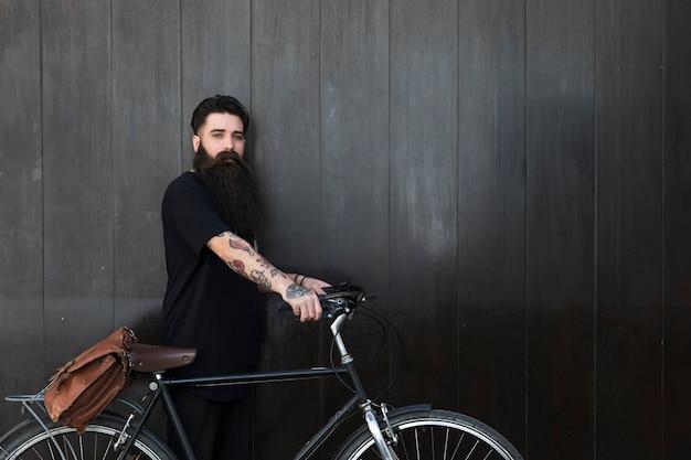 Barbudo jovem com sua bicicleta na frente da parede de madeira preta