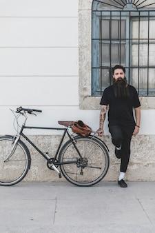 Barbudo jovem em pé perto da bicicleta
