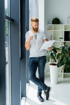 Barbudo jovem empresário trabalhando em um escritório moderno. homem vestindo camiseta branca e fazendo anotações nos documentos.