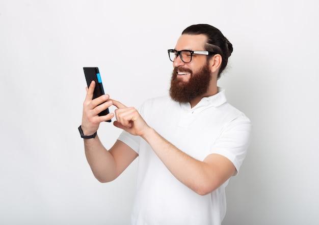 Barbudo jovem inteligente está usando um tablet que ele está segurando.