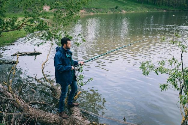 Barbudo jovem pesca no lago