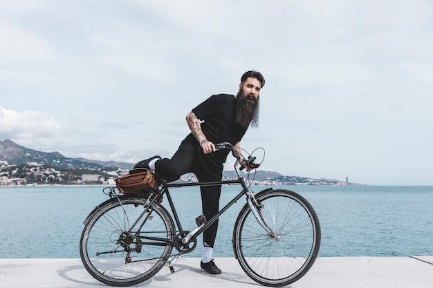 Barbudo jovem sentado na bicicleta perto da costa