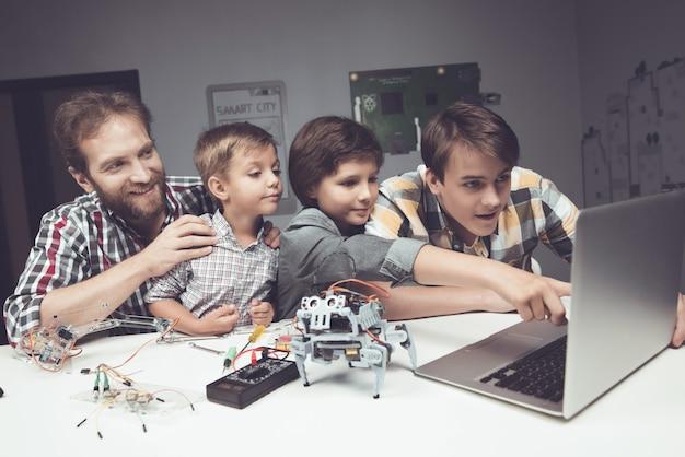 Barbudo pai e filhos construindo robô em casa