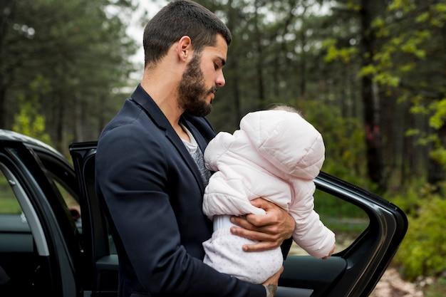 Barbudo pai segurando o bebê perto de carro
