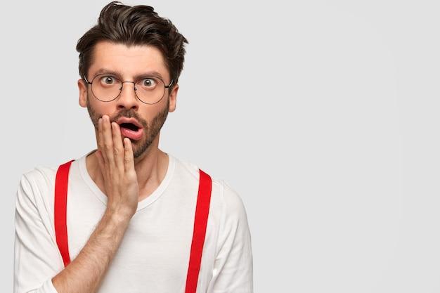 Barbudo surpreso com expressão de espanto, mantém a mão na bochecha e abre a boca, tem rosto desagradável, vestido com suéter branco e suspensórios vermelhos