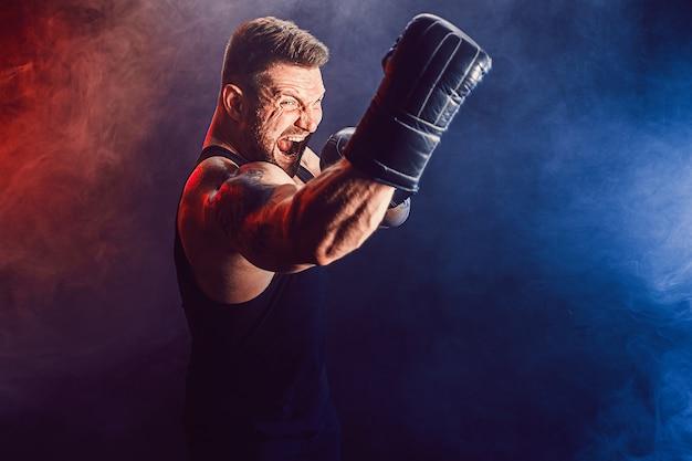 Barbudo tatuado desportista muay thai boxer em camiseta preta e luvas de boxe lutando na parede escura com fumaça. conceito de esporte.