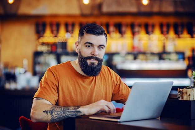 Barbudo tatuado jovem hippie caucasiano sentado no café e trabalhando em projeto freelance.
