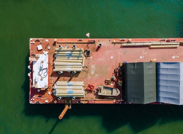 Barcaça em um navio de construção na passagem de carga de estruturas metálicas e tubos de navios e barcaças
