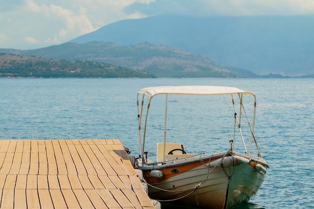 Barco a motor à deriva na costa do mar azul no cais