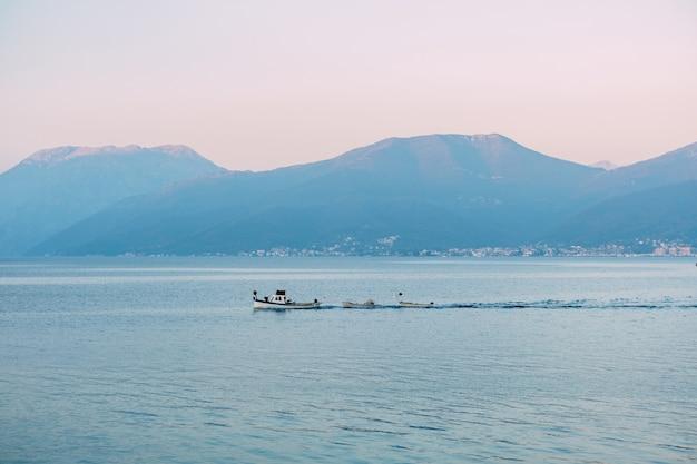 Barco a motor branco reboca pequenos barcos a remo no mar ao longo das montanhas ao pôr do sol