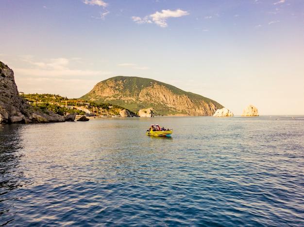 Barco a motor de luxo perto da costa do mar rock na baía da cidade de europa
