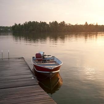 Barco a motor na doca no lago dos bosques, ontário