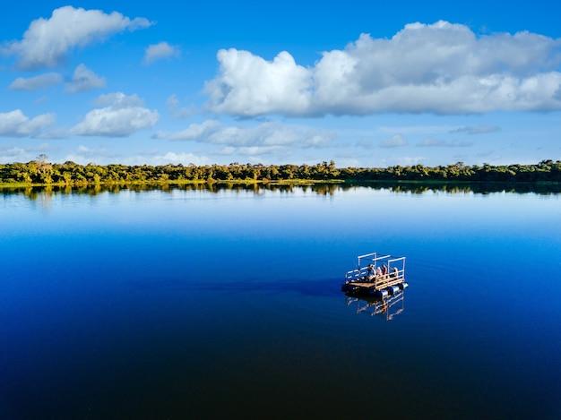 Barco a motor no lago cercado por belas árvores verdes sob um céu nublado