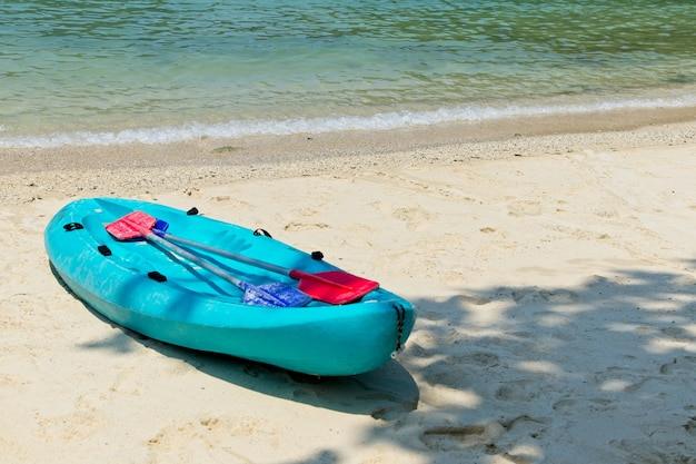 Barco a remo azul na praia com o lindo oceano