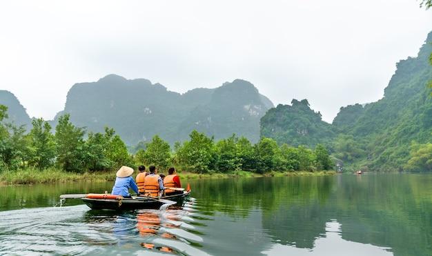 Barco a remo turístico no complexo paisagístico de trang an, na província de ninh binh, no vietnã