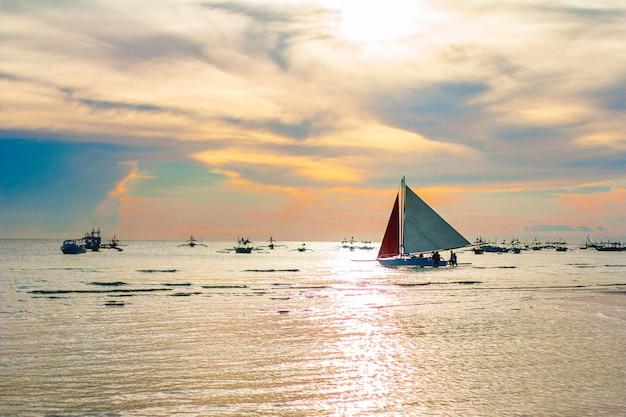 Barco à vela ao pôr do sol na ilha de boracay