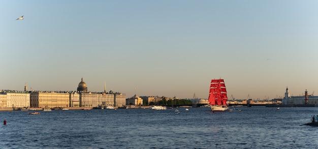 Barco à vela com velas vermelhas no rio neva, são petersburgo. velas escarlate de férias. rússia. veleiro navegando no rio neva. férias na federação russa.