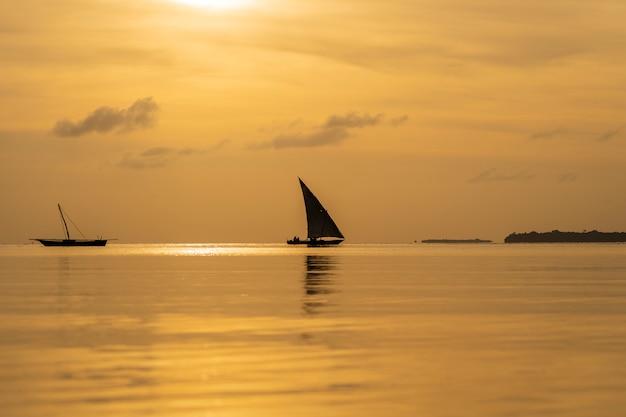 Barco à vela de pesca tradicional durante o pôr do sol no oceano índico na ilha de zanzibar, tanzânia, áfrica
