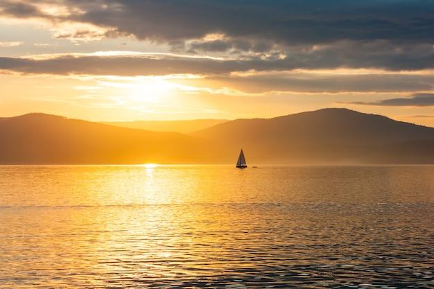 Barco à vela no lago ao pôr do sol no horizonte