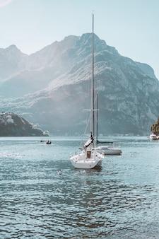 Barco à vela perto da costa do lago de como, na itália, bela paisagem montanhosa