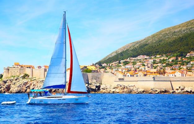Barco a vela perto das muralhas da cidade velha de dubrovnik, croácia