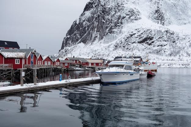 Barco ancorado no cais com vila de pescadores em lofoten