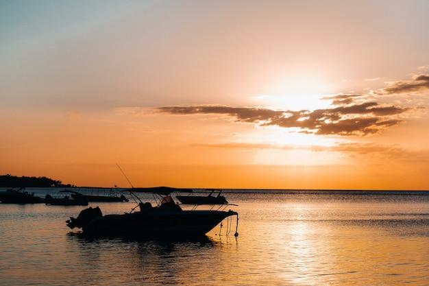 Barco ao pôr do sol no oceano índico, na costa da maurícia.