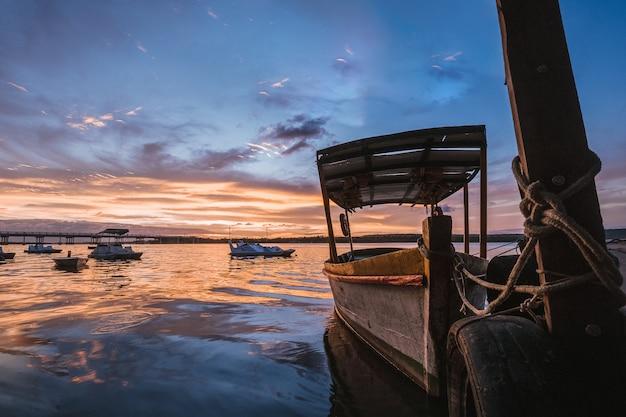 Barco artesanal de madeira no mar sob um céu nublado e luz do sol durante o pôr do sol