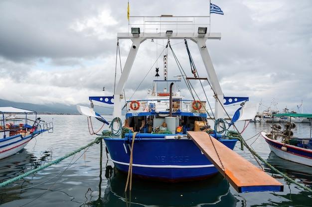 Barco atracado em azul e branco com ponte rebaixada
